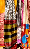 colorful fabrics and shawls at a market stall