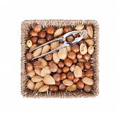 stock photo of mixed nut  - Mixed nuts in a woven basket with nut cracker isolated on white - JPG