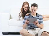 A beautiful Couple on sofa with digital tablet