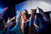 party, holidays, celebration, nightlife and people concept - happy young women singing karaoke in night club