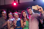 party, holidays, technology, nightlife and people concept - smiling friends with glasses of champagne and smartphone taking selfie in club
