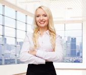business, style and people concept - smiling businesswoman, student or secretary over office window with city view background