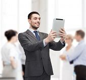 business, communication, modern technology and office concept - smiling buisnessman with tablet pc computer