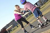 Active family - mother and kid having fun, rollerblading outdoor