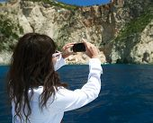 image of cave woman  - young woman photographs the island in Greece - JPG