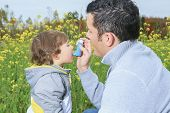 stock photo of inhalant  - A dad give inhaler for respiratory system issues - JPG