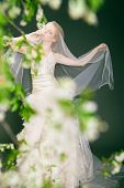 Dreamy beautiful blonde bride walking alone in the park