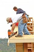 picture of rafters  - Framing contractor installing roof sheeting over rafters on a new commercial residential construction project - JPG