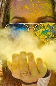 picture of holi  - woman blowing yellow Holi Powder at camera - JPG