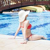 picture of sunbather  - Young woman sunbathing at the swimming pool - JPG