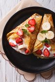 image of crepes  - homemade crepes with fresh strawberries bananas and cream close - JPG