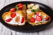 picture of crepes  - Two crepes with fresh strawberries bananas and cream close - JPG