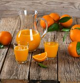 picture of pitcher  - Composition with two glasses of orange juice fruits and pitcher on a old wooden table - JPG