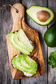 picture of sesame seed  - sandwiches with rye bread sliced avocado sesame seeds on wooden cutting board - JPG