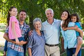 pic of extended family  - Extended family smiling at the camera on a sunny day - JPG