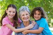 stock photo of extended family  - Extended family smiling and kissing in a park on a sunny day - JPG
