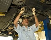 picture of hookup  - a automechanic works on a automobile from underneath - JPG