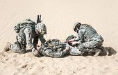 stock photo of medevac  - United States paratroopers airborne infantrymen in the desert rescuing their brother - JPG