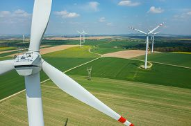 stock photo of windmills  - Aerial view on the windmills on the green field - JPG