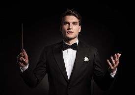 stock photo of conduction  - Young handsome man conducting an orchestra - JPG