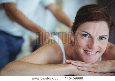 Woman receiving back massage from physiotherapist in clinic