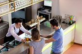 High angle view of barkeeper serving beer to couple in bar poster