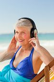 Retired Woman Listening To Music At The Beach