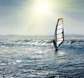 Windsurfer on sea wave under sunlight
