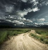 image of dirt road  - Road in field and stormy clouds - JPG
