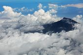 Mountain Rinjani among clouds. View frome plane. Lombok island. Indonesia