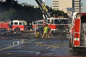 picture of firehose  - Exausted Fire Men taking control of a building fire - JPG