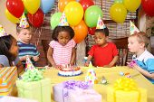 image of birthday party  - Young girl blowing out candles at birthday party - JPG