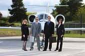 Group of business people with corporate jet in background