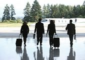 Group of businesspeople walking to corporate jet