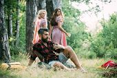 Picnic At Sunny Meadow. Two Girls Looking Back At Man Sitting On Grass. Brutal Bearded Man Drinking  poster
