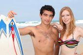 paar Teenager posiert mit Surfbrett direkt am Meer