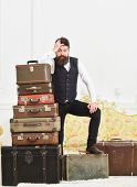 Macho Elegant On Disappointed Face Standing Near Pile Of Vintage Suitcase. Man, Butler With Beard An poster