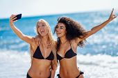 Two Women Taking Selfie Photograph With Smartphone In The Beach poster