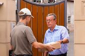 Postal service - delivery of a package; the postman is giving the package to the customer in front o