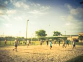 Blurred Indian People Playing Volleyball On Open Air Sand Court In Texas, Usa poster