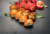 Sushi with chopsticks. Sushi roll japanese food in restaurant. California Sushi roll set with salmon poster