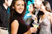 foto of christmas party  - Young friendly woman looking at camera while a party - JPG