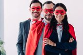 Super Businesspeople In Masks And Capes Looking At Camera In Office poster