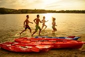 Friends Playing and Having Fun in the Water on the Beach near Kayaks under the Dramatic Evening Sky  poster