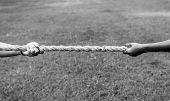 Closeup of hand pulling the rope in tug of war game poster