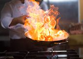 Chef cooking and doing flambe on food in restaurant kitchen poster