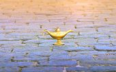 Bronze Aladdin Lamp On Cobbles. Fairy Tale Oriental Concept Of Fulfillment Of Desires. poster
