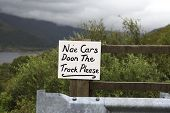 stock photo of dialect  - Gaelic text in Scotland on a sign meaning no cars down the track please with a loch in the background - JPG