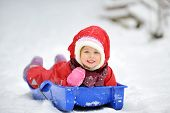 image of snow-slide  - Little girl on sleigh in winter time - JPG