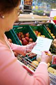 stock photo of grocery-shopping  - Image of senior woman looking at product list with goods in cart near by - JPG